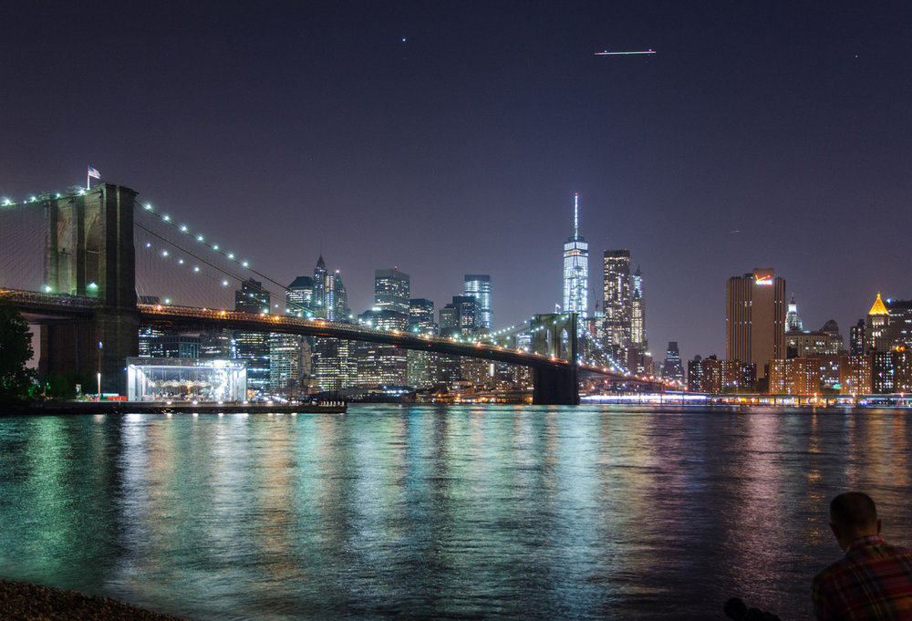 A view of Manhattan and the Brooklyn Bridge at night from Brooklyn Bridge Park, NYC.