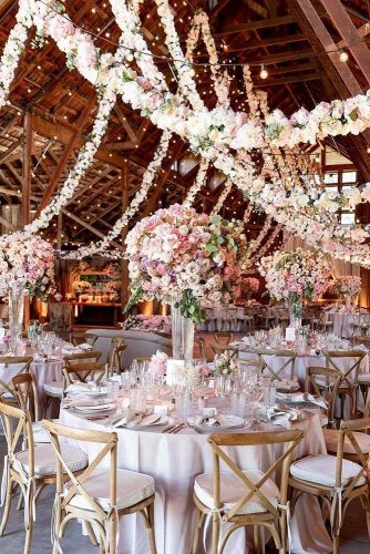 wedding-trends-2019-elegant-wedding-reception-in-barn-with-tall-centrpieces-pale-pink-flower-handing-garlang-larissaclevelandphoto-334x500.jpg