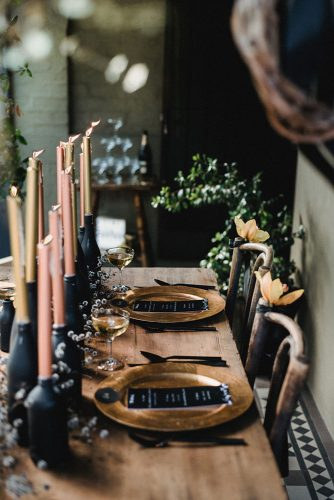 wedding-trends-2019-moody-table-with-candles-in-bottles-with-flowers-and-gold-plates-cj-williams-334x500.jpg