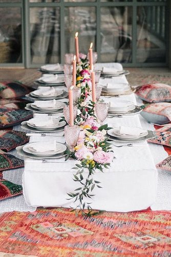 wedding-trends-2019-low-boho-table-pillows-around-eclectic-pink-glasses-candles-flowers-and-greenery-ugophotography-334x500.jpg