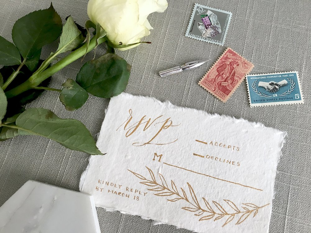 "This RSVP card shows the traditional approach of adding an ""M"" with a line next to it for the guests to fill in their names when they reply! I calligraphed this RSVP card on  Fabulous Fancy Pants  paper with gold ink from  Fox & Quills  for a styled shoot."