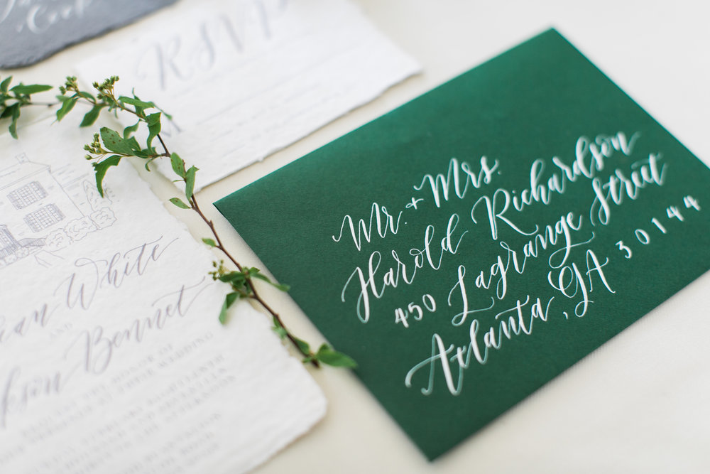 Calligraphy addressing in white ink adds an ethereal and unique touch to this wedding suite! Photo by Alexis June.