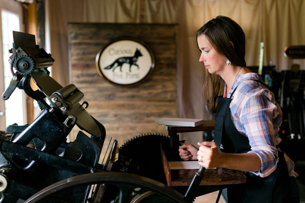 Cathleen of Curious Fox Press monitors her letterpress printing job.  LOVE KNOT PHOTO.