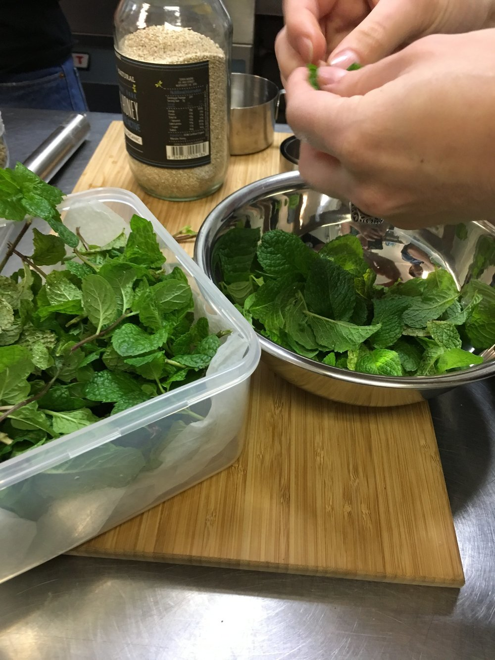 Locally sourced mint leaves being picked and washed in preparation for being added to the salad.