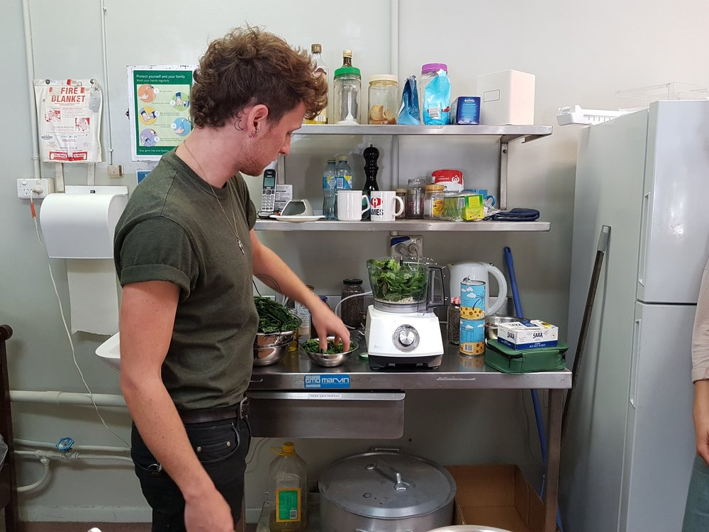 Michael putting the first batch of leafy greens into the food processor.