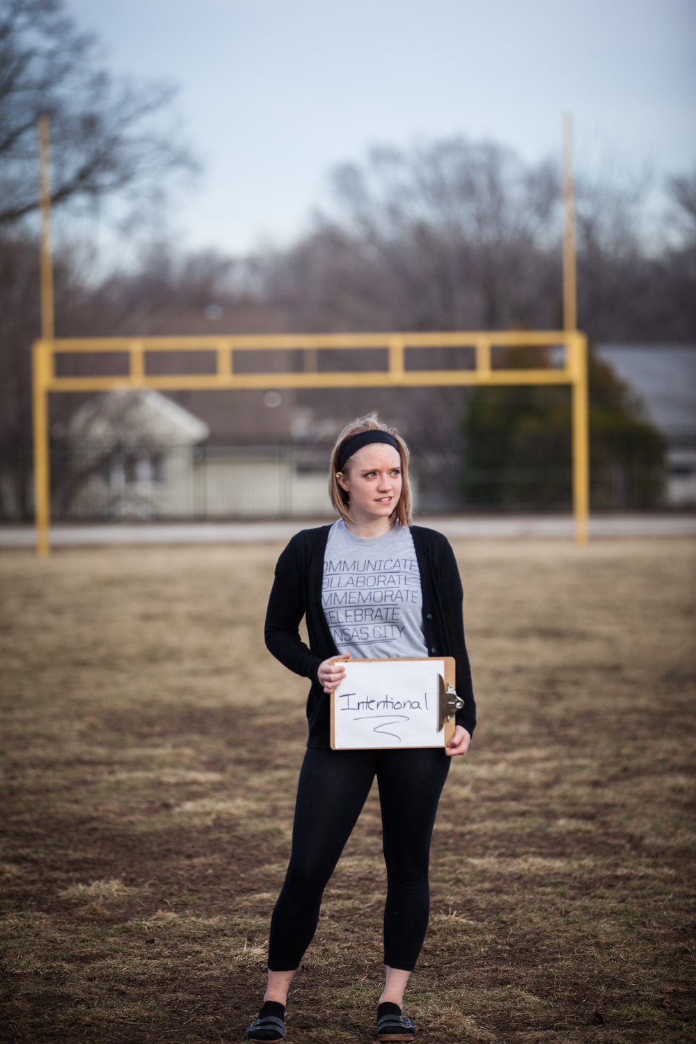 Young woman holding a sign saying intentional.