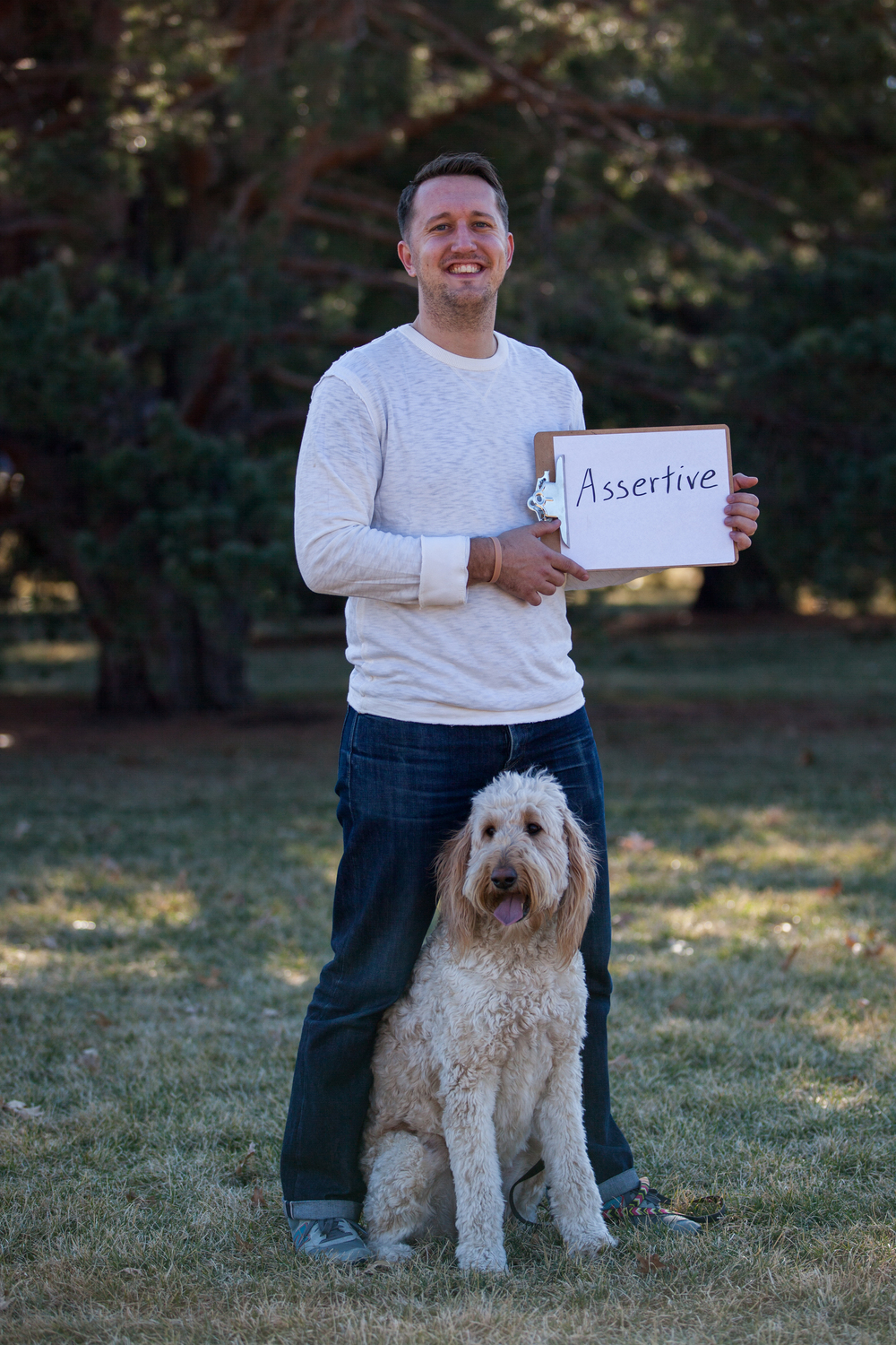 Man standing with his dog holding a sign saying assertive.