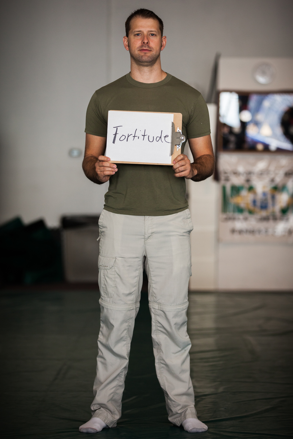 Man holding sign saying fortitude.