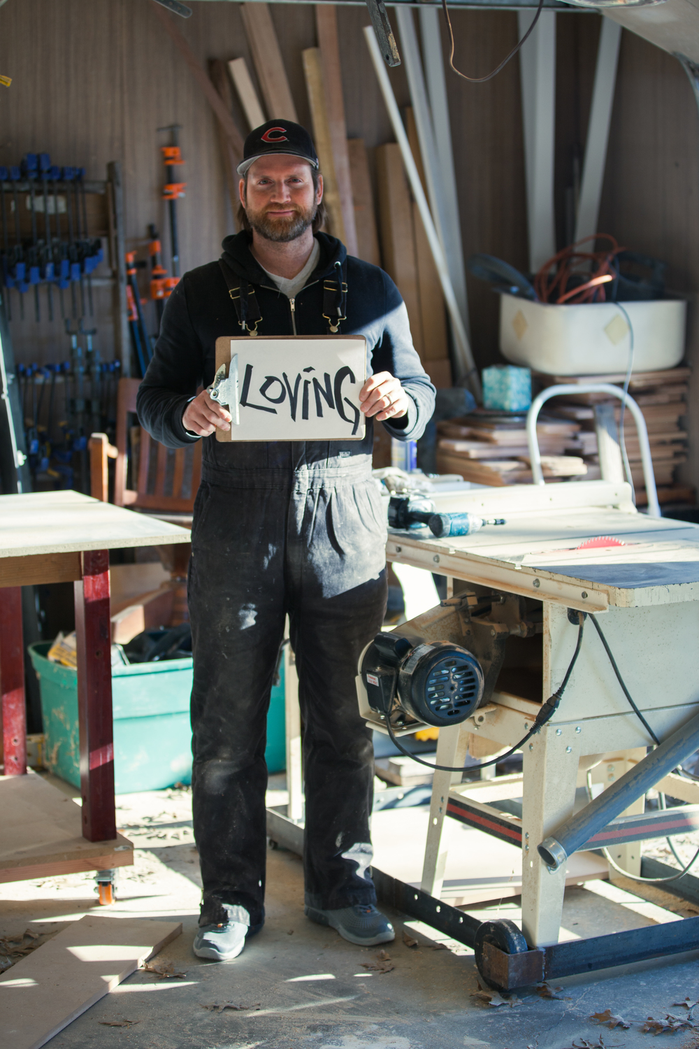 Man holding a sign saying loving in a woodshop.