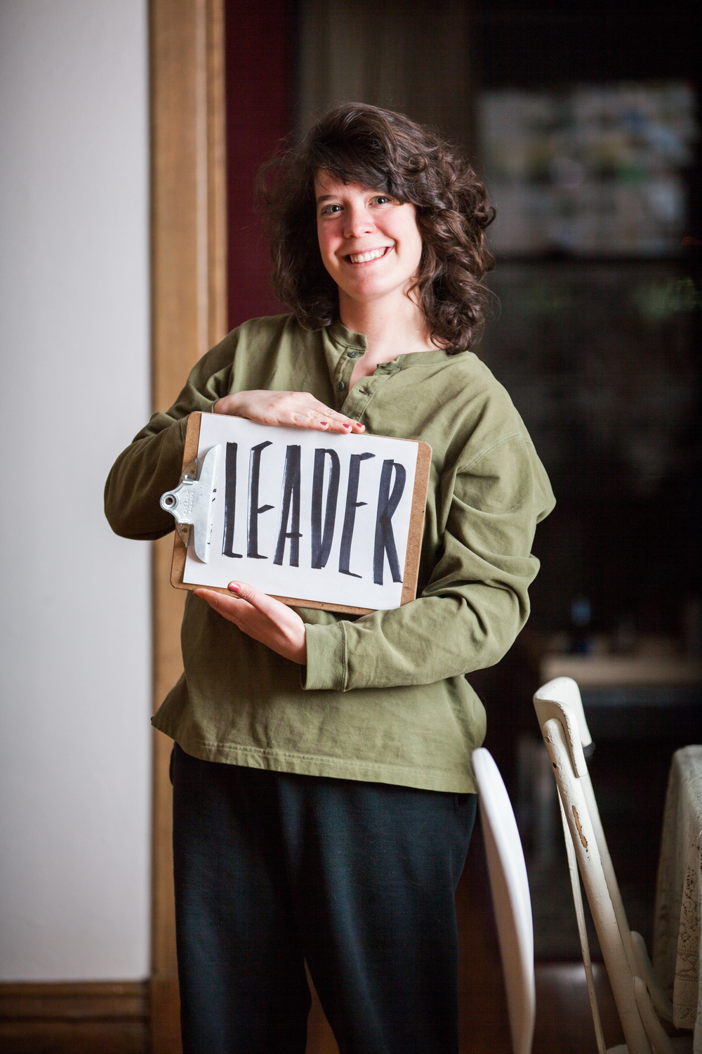 Woman holding a sign saying leader.