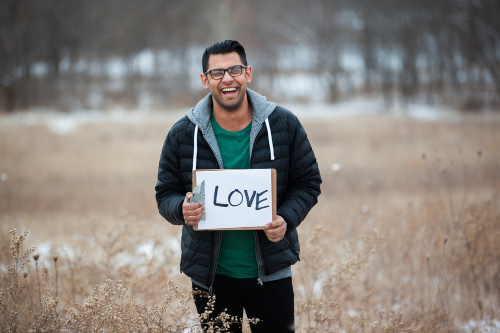Man holding a sign saying love in a snowy field.