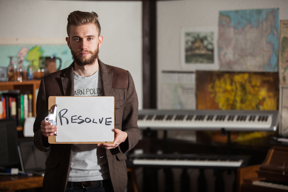 Man holding a sign saying resolve with keyboards in the background.