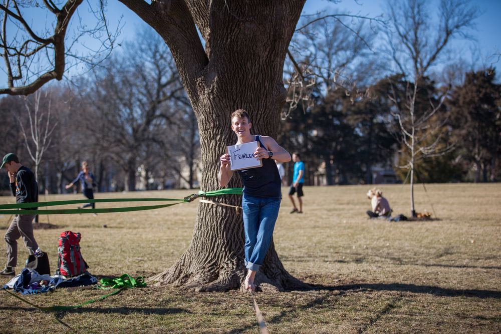Man standing on a slack line while holding a sign saying fearless.