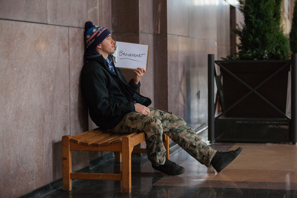 Young man sitting on a bench holding a sign saying braveheart.