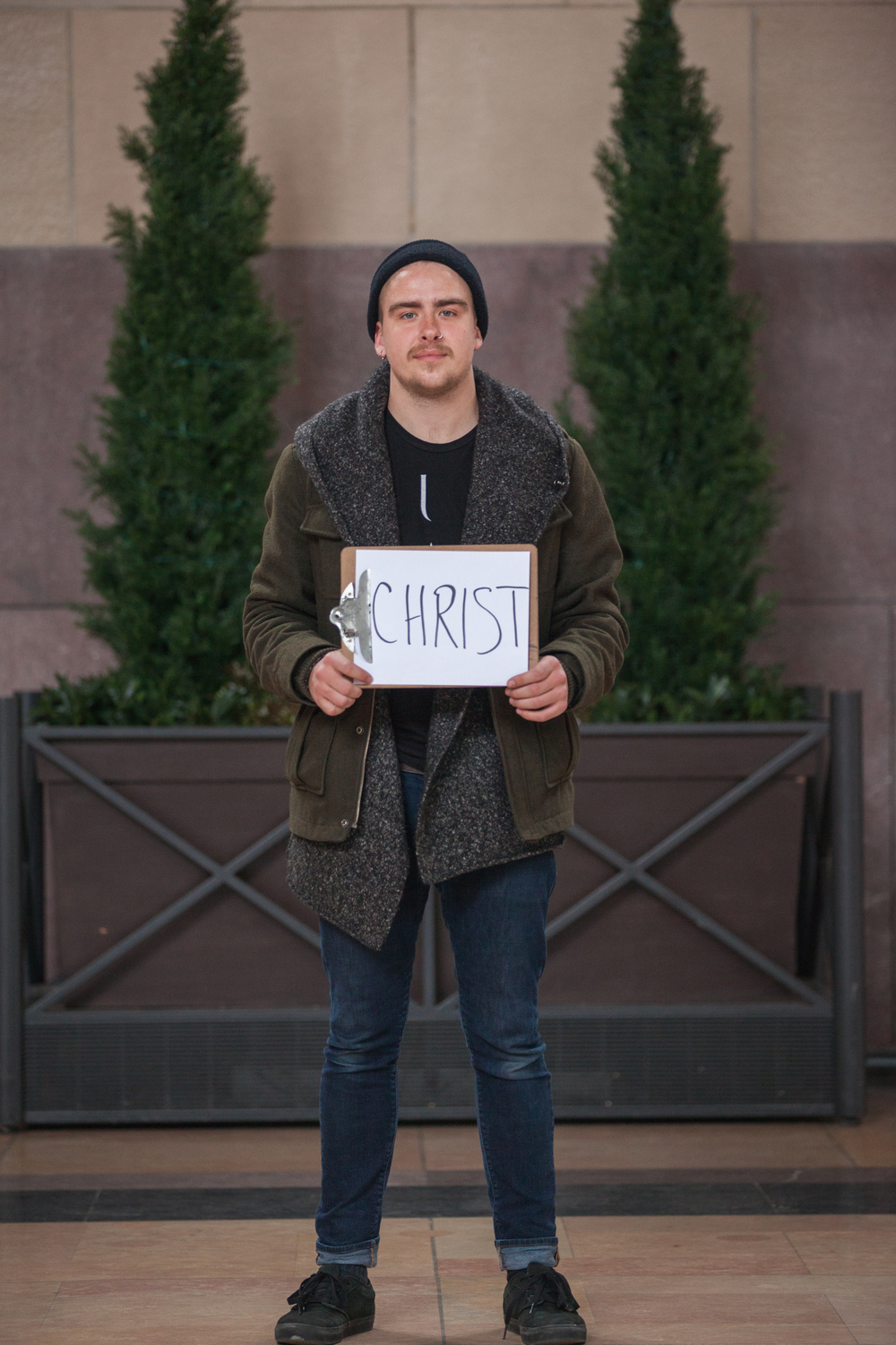 Man holding a sign saying Christ.