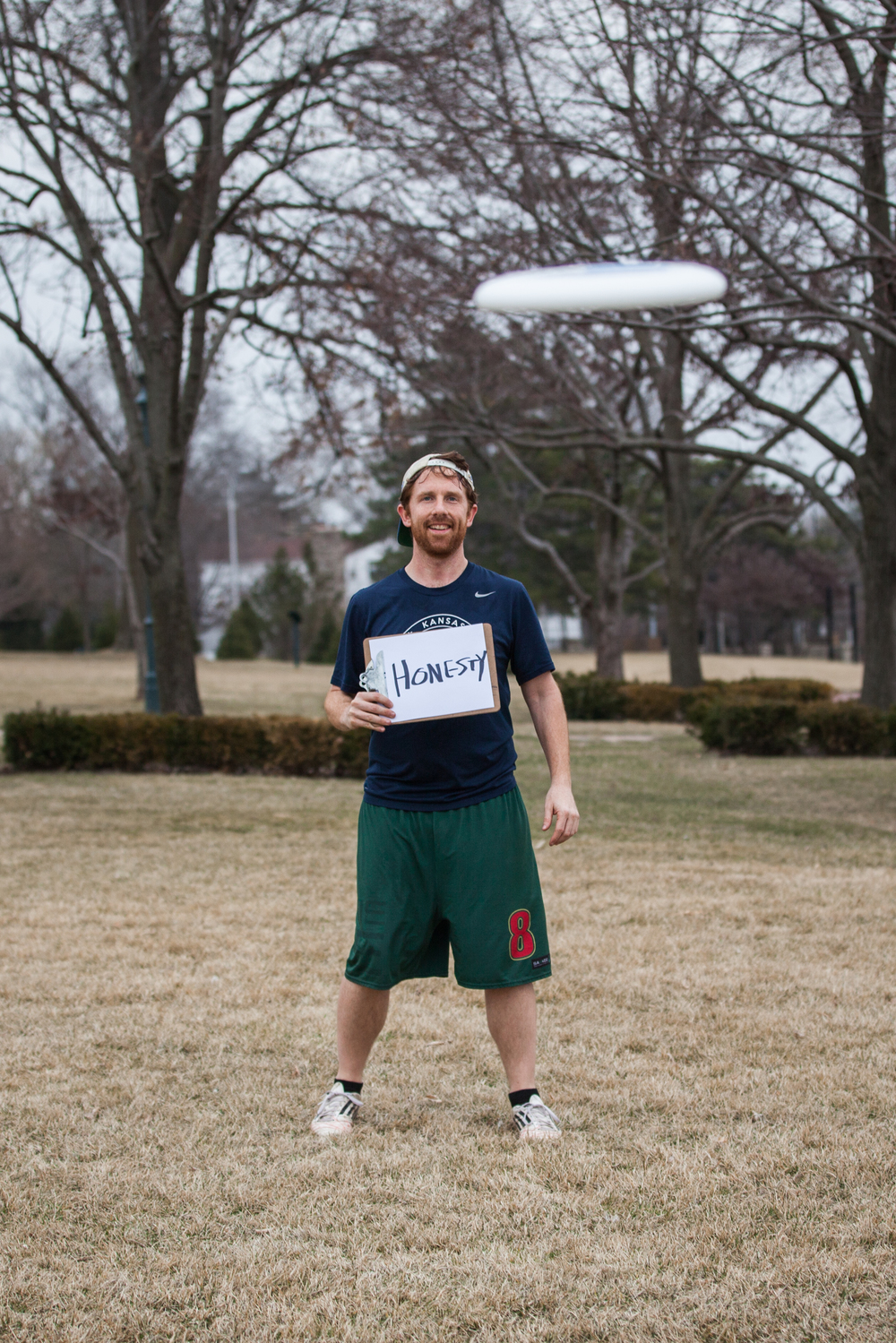 Man holding a sign saying honesty with a frisbee flying at him.