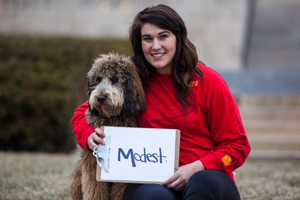 Woman holding a sign saying modest with a dog next to her.