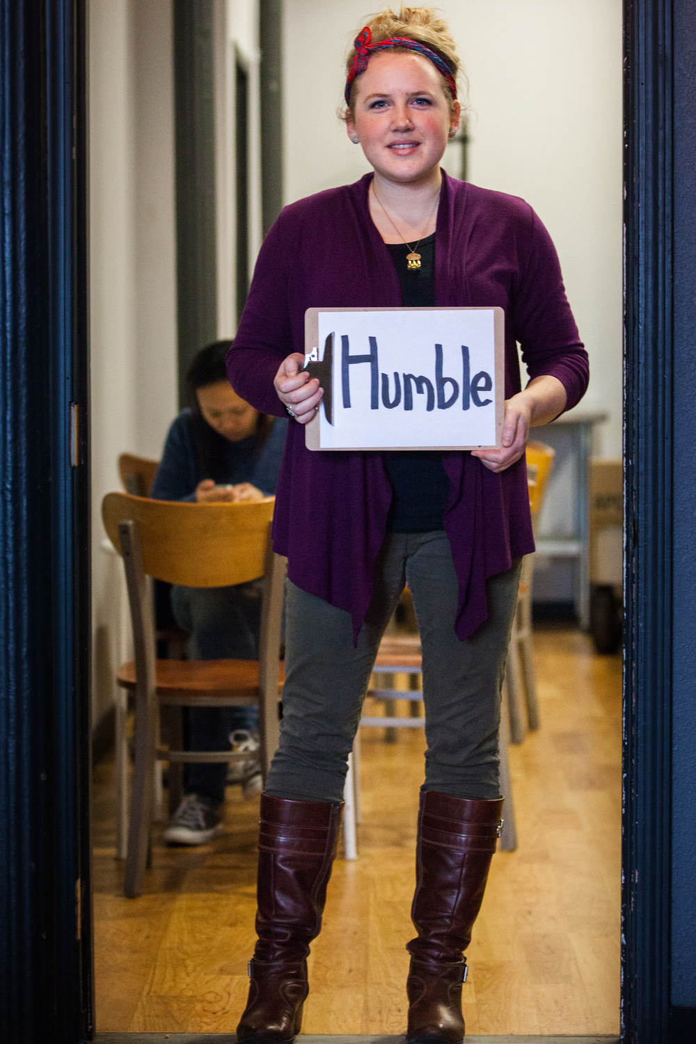 Woman holding a sign saying humble.