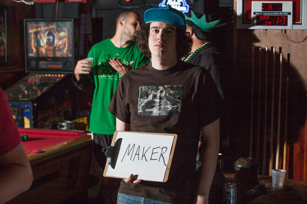 Man holding a sign in a bar that says maker.