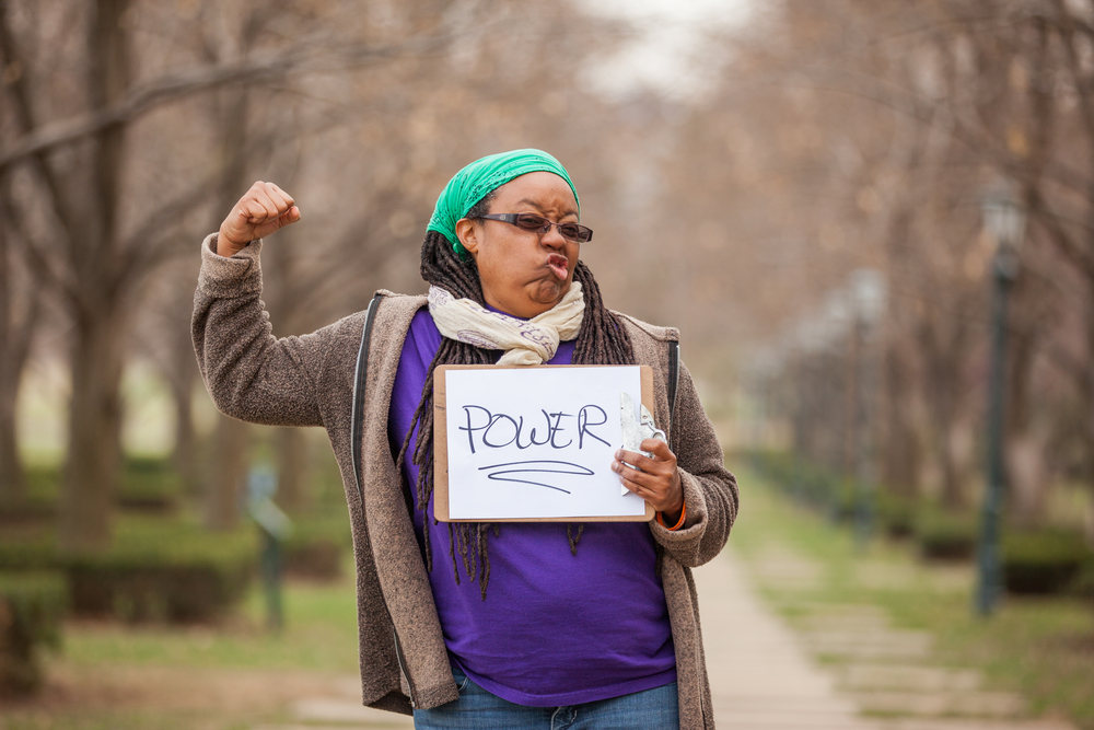 Woman holding a sign that says power.
