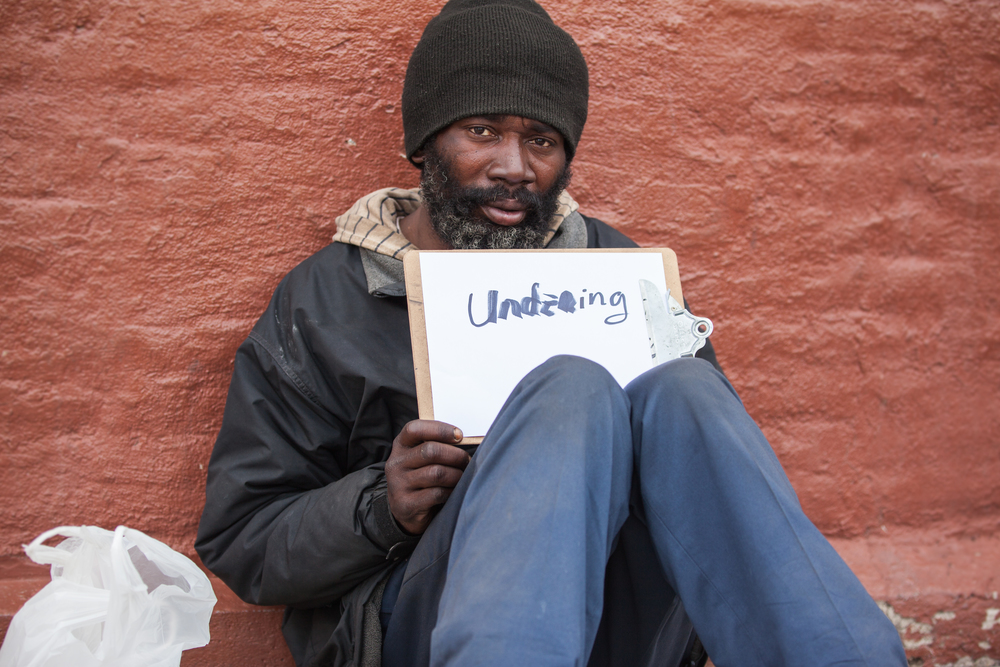 Man holding a sign that says understanding while sitting on the ground.