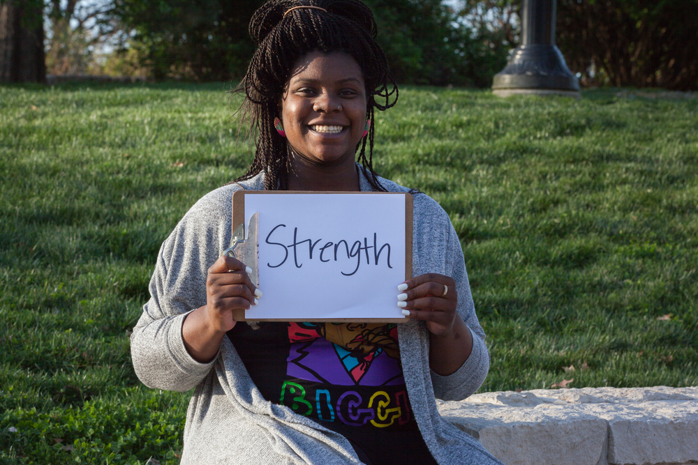 Woman holding a sign that says strength.