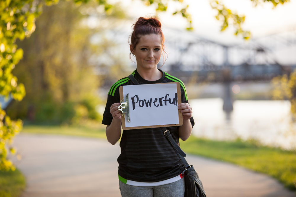 Young woman holding a sign saying powerful.