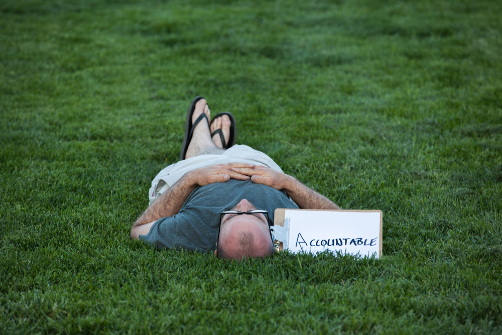 Man laying in the grass with a sign by him saying accountable.