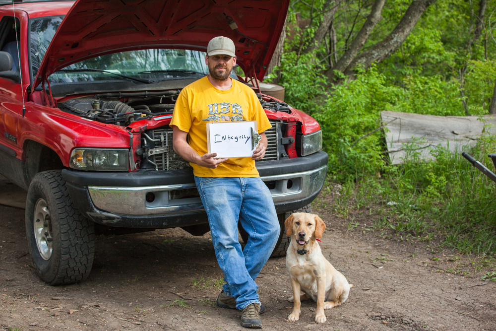 Man leaning against a truck with his dog sitting on the ground next to him holding a sign that says integrity.