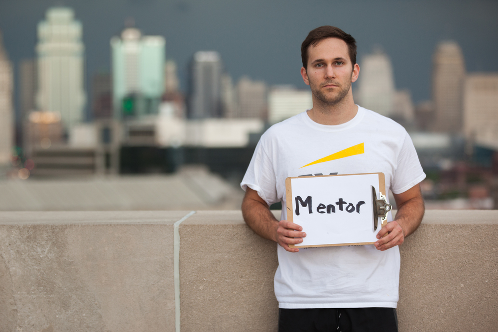 Man holding a sign that says mentor while leaning against a wall.