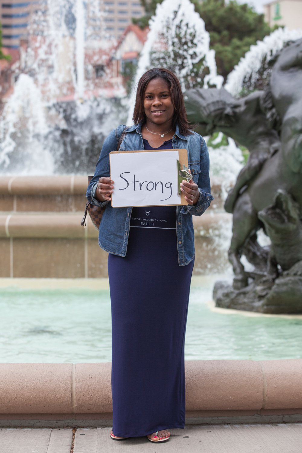 Woman holding a sign saying strong while standing next to a fountain.