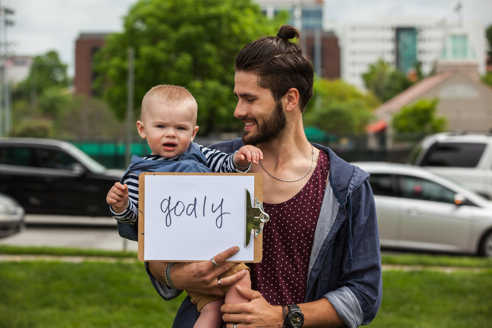 Man holding a his child and a sign that says godly.