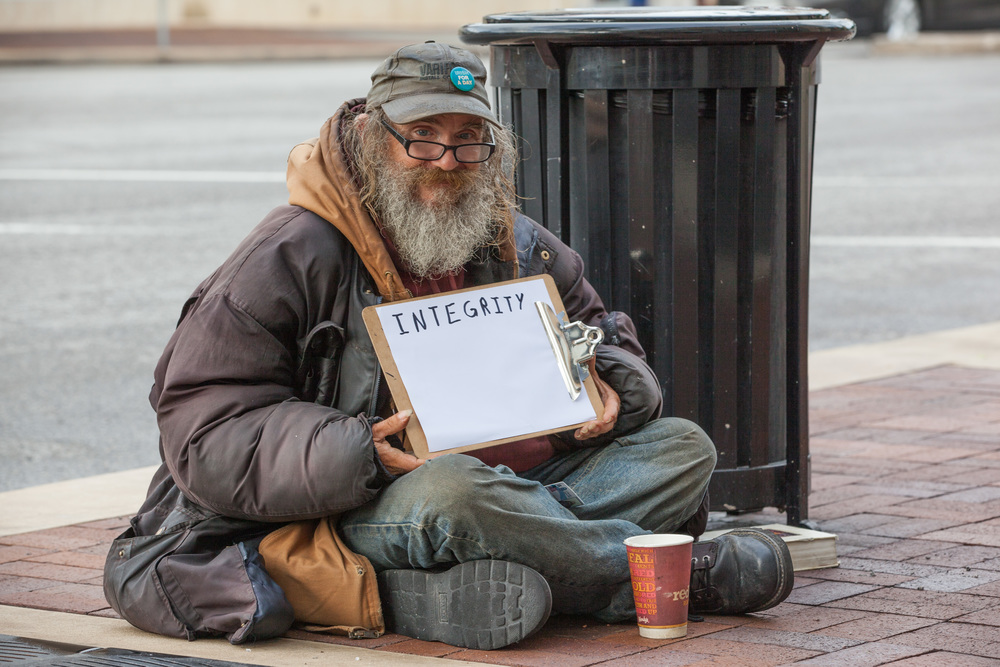 Man holding a sign that says integrity while sitting on the ground.