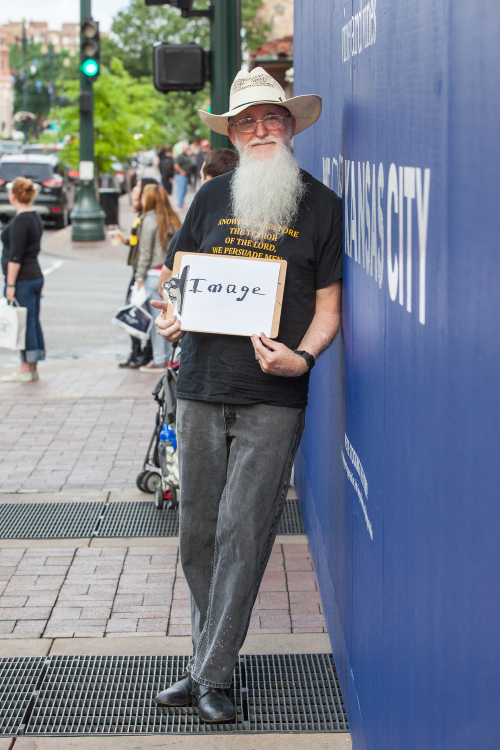 Man leaning against a wall holding a sign that says image.