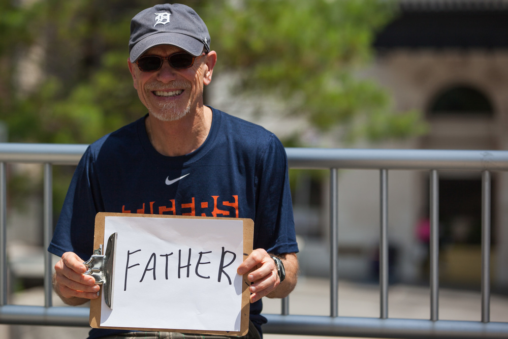 Man holding a sign that says father.