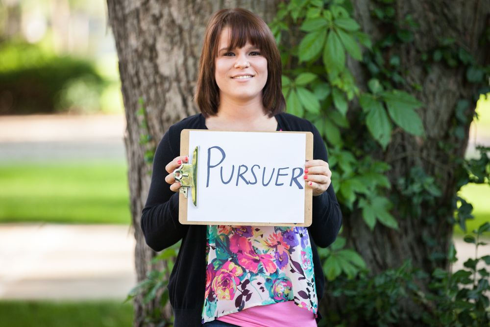 Woman holding a sign that says pursuer.