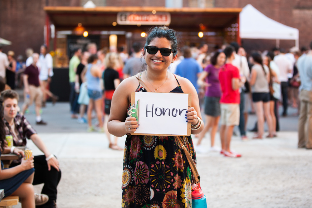 Woman holding a sign with the word honor on it.