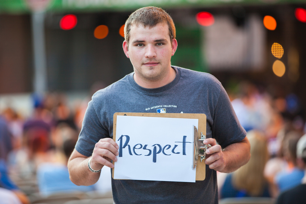 Young man holding a sign that says respect.