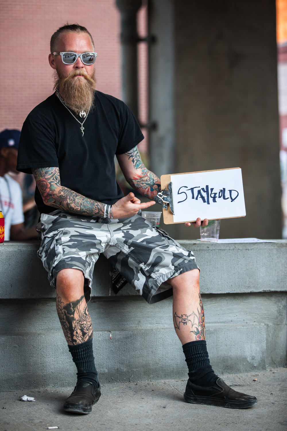 Man sitting while holding a sign that says stay gold.
