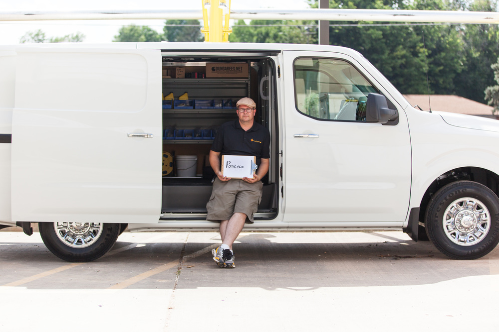 Man sitting in a van holding a sign that says patience.