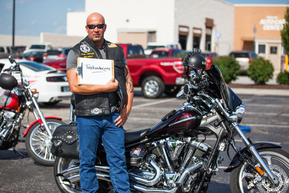 Muscular man holding a a sign that says testosterone while standing by a motorcycle.
