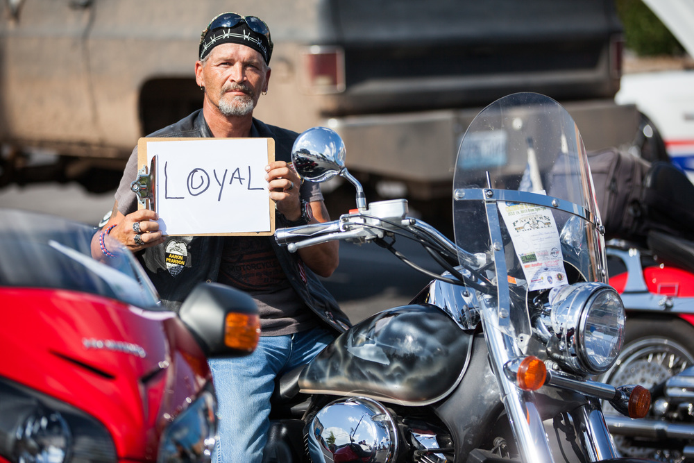 Man sitting on a motorcycle holding a sign that says loyal.