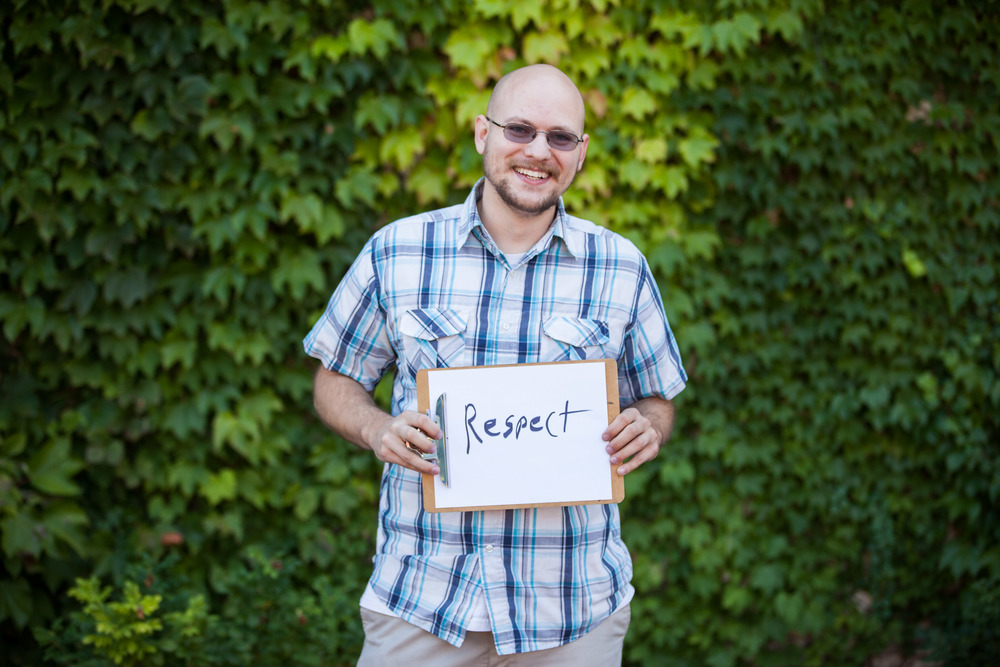Man holding a sign that says respect.