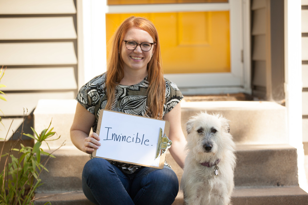 Woman sitting with her dog on some stairs while holding a sign that says invincible.