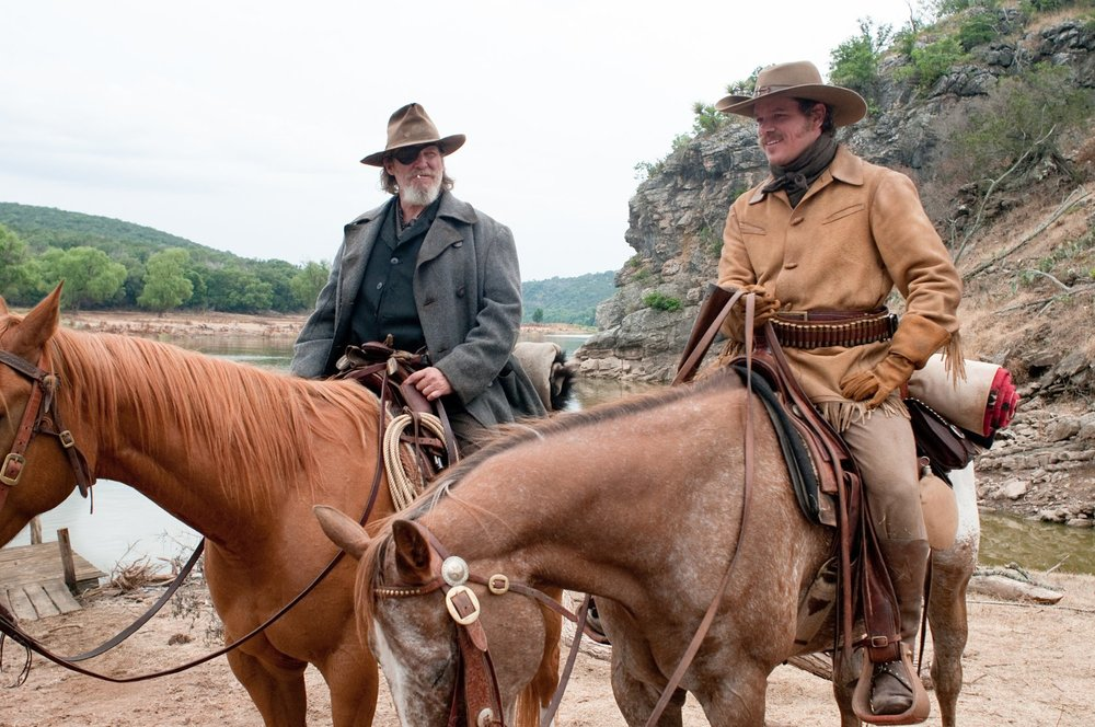"""Picture from the movie """"True Grit"""" two men on hoarses."""