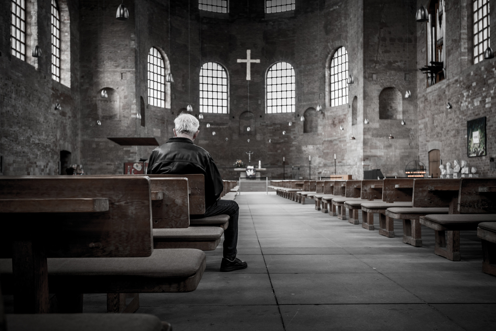 Man sitting in a bench in a cathedral.