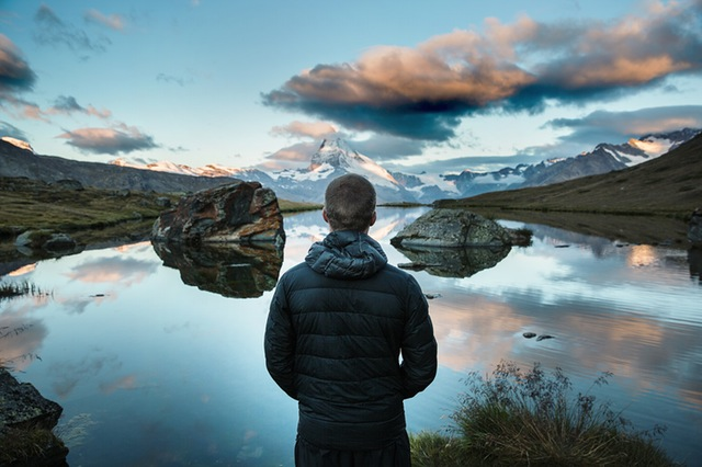 Man observinge a sunset with mountains and lake in front of him.