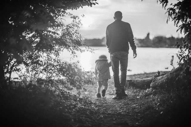Man walking with child while holding its hand.