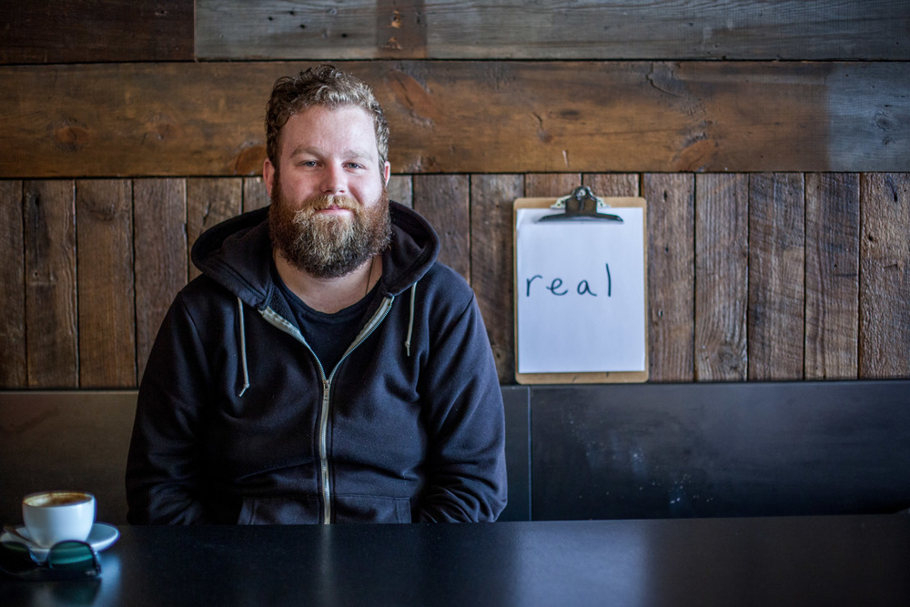 Man sitting in a coffee shop with a sign near him saying real.