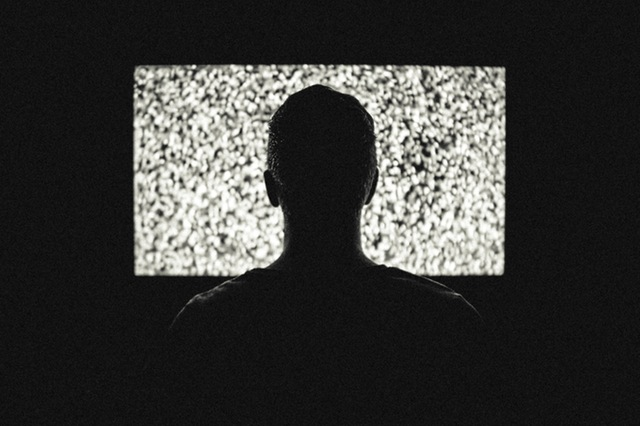 Man watching a TV that is just static.